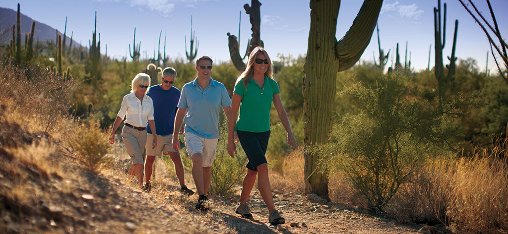 Group walking on trail. The Ritz-Carlton Residences, Dove Mountain incorporates 25 miles of trails winding from the community trailhead through the Tortolita Mountains and Wild Burro Canyon.