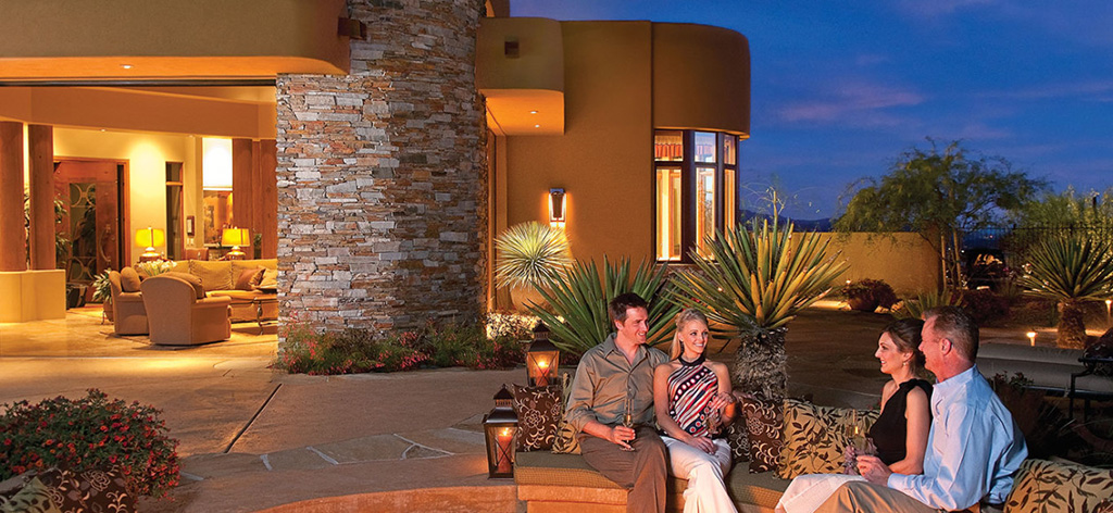 Two couples sitting outside of a luxury home in Dove Mountain.
