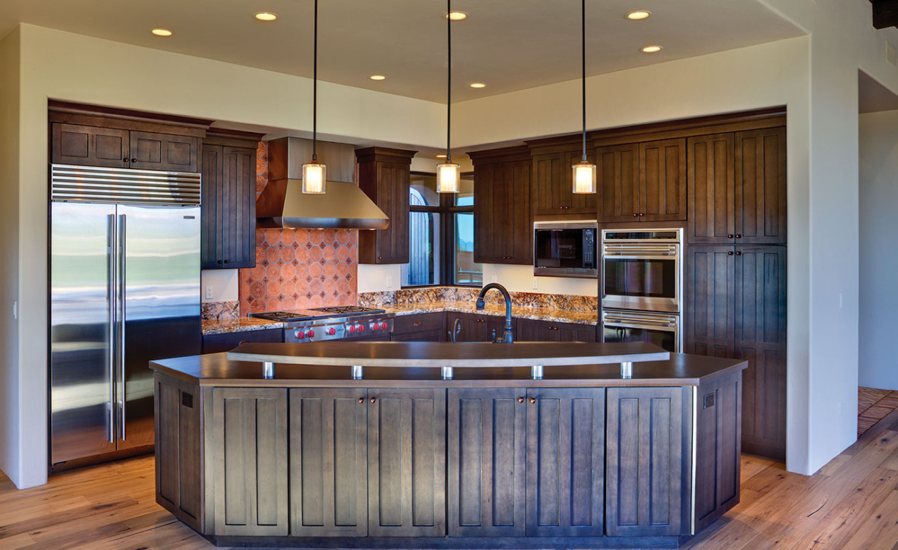 Front view of luxury kitchen with large island and dark wood cabinets. Visit our Dove Mountain homes today.