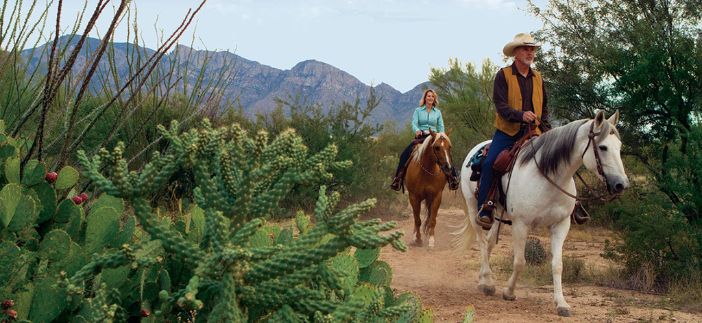 Woman and man horseback riding in Dove Mountain, Marana.