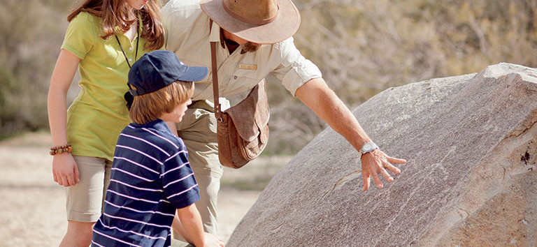 Tour guide shows children ancient markings along Dove Mountain hiking trails.